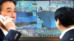 A man watches TV news comparing the YouTube footage with an image of the Chinese boat involved in the collision on 5 November 2010