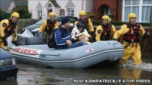Rescue crews with woman and baby in a lifeboat