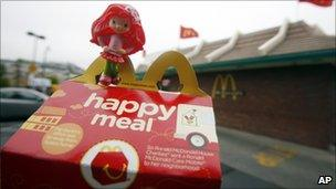 A toy sitting atop a fast-food meal outside a McDonald's restaurant
