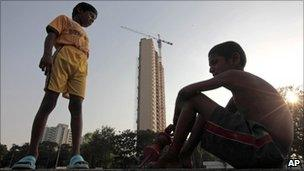 Indian boys chat in the backdrop of the Adarsh Housing Society apartments in Mumbai on 1 November 2010