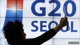 A woman photographs herself in front of a G20 Seoul sign
