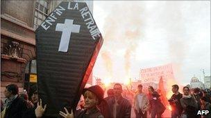 "Demonstrators in Lyon, central France, carry a mock coffin marked ""Finally retiring"", 6 November"