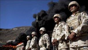 Soldiers stand in formation next to packages of marijuana that are being incinerated in Tijuana, Mexico, on 10 November