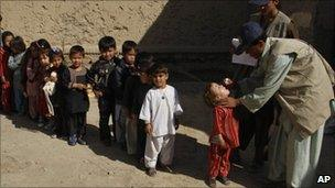 An Afghan health worker gives a polio vaccination to a child, as other children stand on line during a polio campaign in Kandahar province, south of Kabul, Afghanistan on Sunday, Nov 7, 2010