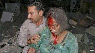 A man helps a woman from the scene of the blast in Karachi, Pakistan