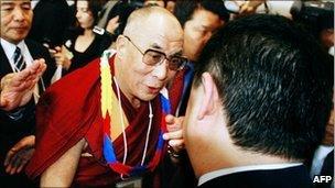 Tibetan spiritual leader Dalai Lama shakes hands with Chinese activist Wu'er Kaixi