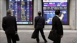 Businessmen check stock market figures on a signboard in Tokyo on 14 October 2010