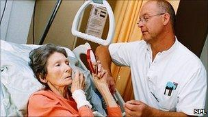 A nurse helping a terminally ill patient put on some make-up