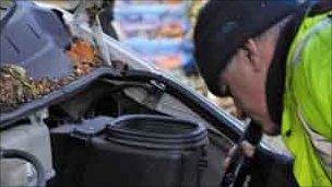 A vehicle inspector examines an engine