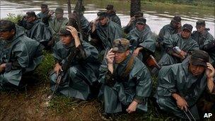 Nicaraguan troops kneel as a helicopter takes off beside the San Juan river