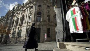 A nun passes by a Bank of Portugal branch in Porto (17 Nov 2010)