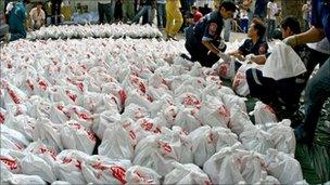 Members of a rescue foundation carry bags of corpses at the mortuary storage room of a Buddhist temple in Bangkok