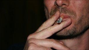 A young man smoking outside a pub