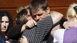 Mine blast survivor Daniel Rockhouse (centre) hugs family members following their briefing with officials in Greymouth (22 November 2010)