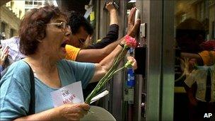 Demonstrators bang on the door of a bank in the financial district of Buenos Aires, February 2002