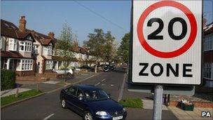A car passing a 20mph speed limit sign in Morden, south-west London