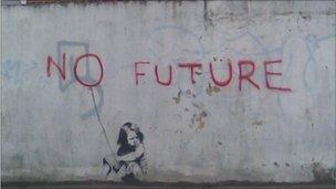 Banksy painting of a child sitting under the words 'no future'