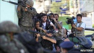 Police and journalists crowd around an operation by security forces in Complexo do Alemao