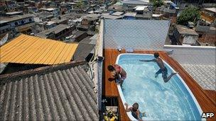 Children play in a swimming pool after the premises owned by an alleged drug dealer were raided by police