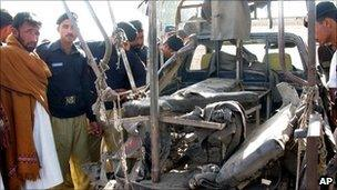 Pakistani police look at a van destroyed by an explosion in Bannu on 30 November 2010
