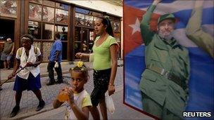 People walk past a poster of Fidel Castro on a bookshop window in Havana
