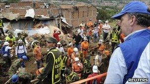 President Juan Manuel Santos looks on as rescuers dig for landslide victims