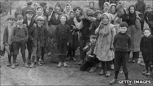 Children, wearing clogs, gather coal in 1921