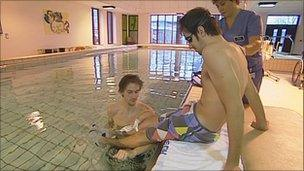Ben getting into the pool with his physiotherapist