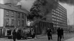 Smoke billows from a building beside Rossville flats after a explosion, August 1969