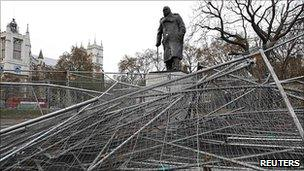 Collapsed metal barricades in front of a statue of William Churchill