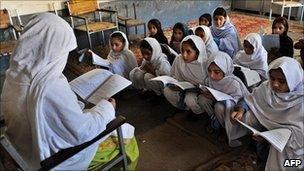 Pakistani female teacher writes on blackboard