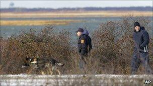 Police search along a road near Cedar Beach