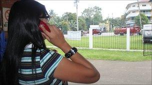 Journalist Malu taking a call at the entrance to her radio station