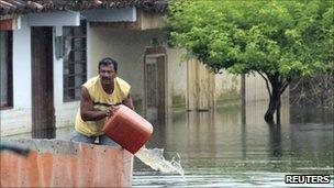 A man removes water from a boat as he moves through flooded streets in La Victoria