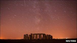 A meteor streaks past stars in the night sky over Stonehenge in Salisbury Plain