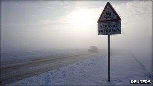 A car drives along a snow-covered road near Cambrai in northern France, 20 December 2010