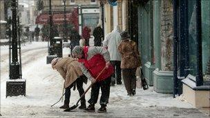 Shopkeepers clearing snow in Wells, Somerset
