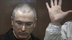 Mikhail Khodorkovsky listens to a verdict from behind bars at a court room in Moscow