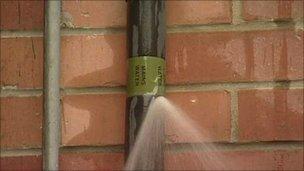 Water spraying from burst pipe
