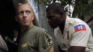 Paul Waggoner being escorted by a Haitian police officer