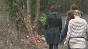 Flowers are left at the scene of the crash
