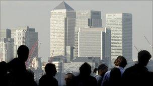 Workers silhouetted in front of London's Canary Wharf skyline