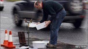 A man fills plastic containers with water in Boucher Road in Belfast
