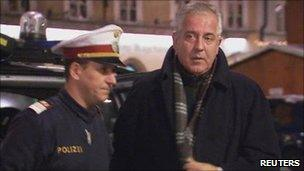 An Austrian policeman accompanies Ivo Sanader after his arrest in Salzburg (10 Dec 2010)
