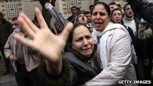 Egyptian Christians mourn outside the Al-Qiddissine church in Alexandria which was hit by a bomb attack on 1 January 2011