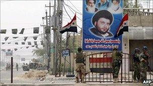 Iraqi soldiers walk past a poster of Moqtada Sadr in Basra (April 2008)