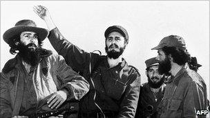 """Cuban rebel leader Fidel Castro (centre), surrounded by the members of his leftist guerrilla movement """"26th of July Movement"""" waves from a jeep 08 January 1959, entering La Havana"""
