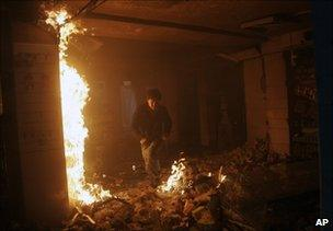 A man runs through the burning supermarket in central Kabul on 28 January 2011