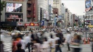 Pedestrians crossing busy street in Tokyo