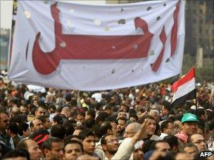 """Protesters hold up a banner saying """"Irhal"""" or """"Depart"""""""